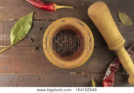 An overhead photo of a mortar with black pepper and a pestle, with bay leaves and dry chili peppers scattered around, on a dark wooden background with copyspace