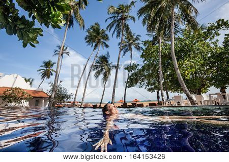 Enjoy the tropical summer. Woman relaxing in the pool water. A beautiful woman with big smile in water in a swimming pool. Relaxation and peace in tropical landscape with palm trees, sea and beach in the distance.