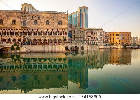 Macau, China - December 9, 2016: The Venetian Resort with luxury shopping centre, mirrored on lake at twilight, the largest casino in the world and the largest single structure hotel building in Asia.