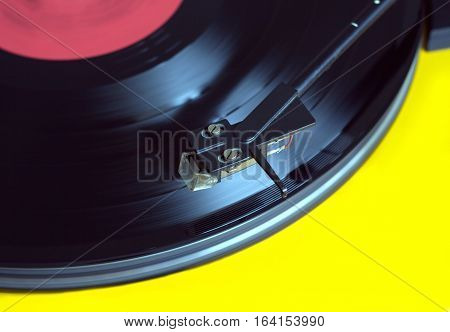 Black long-play vinyl record segment with red label isolated on white background. Photo closeup