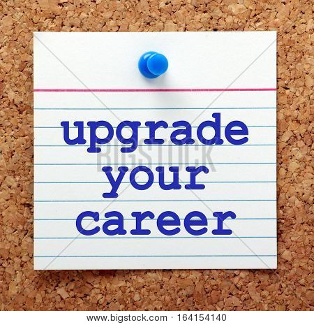 The words Upgrade Your Career in blue text on a note card pinned to a cork notice board as a reminder to progress in your employment
