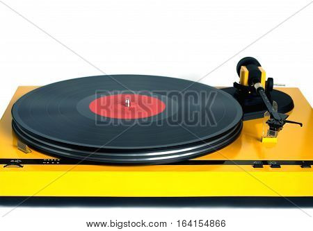Funny turntable in yellow case with rotation vinyl record with red label isolated on white background. Horizontal photo front view closeup