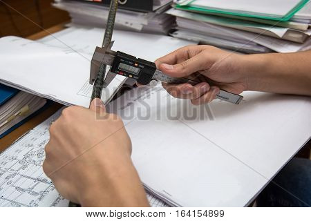 Close-up photography of hand of engineer measures using caliper on blueprints background