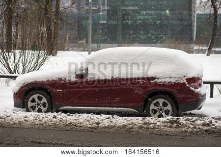Car covered with fresh white snow. A vehicle under the snow