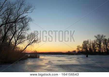 Winter landscape with sunset sky and frozen river. Fisherman on winter lake