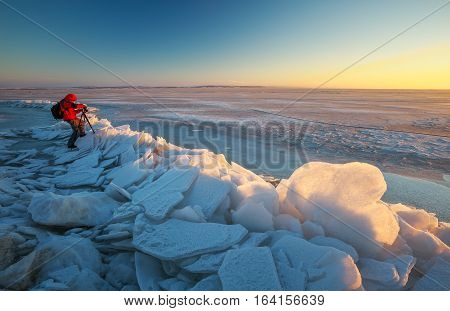 Photographer takes a picture of sunset on a coast of frozen river in winter