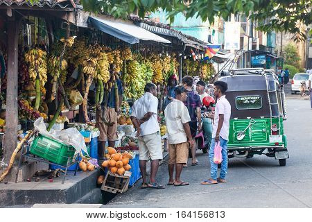 GALLE, SRI LANKA. August 01, 2016: Fruit stalls and people in the street in Galle, Sri Lanka. Some locals talking. A green tuk-tuk on the right. Many bananas for sale.
