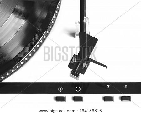 Turntable in silver case with black tonearm and black control buttons ready for vinyl record playing. Top view isolated closeup