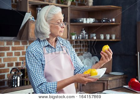 Woman Looking At Lemons In Kitchen