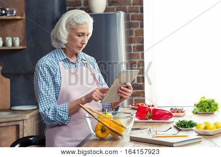 Senior woman using digital tablet in kitchen while preparing vegetable salad
