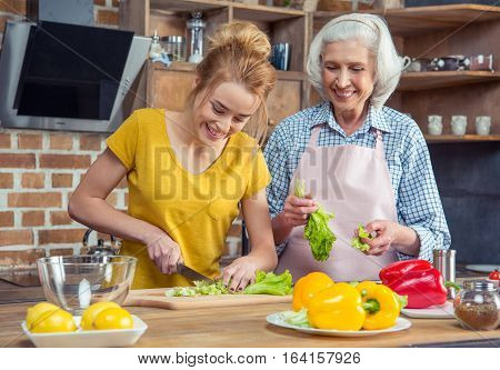 Smiling granddaughter and grandmother cooking together in kitchen