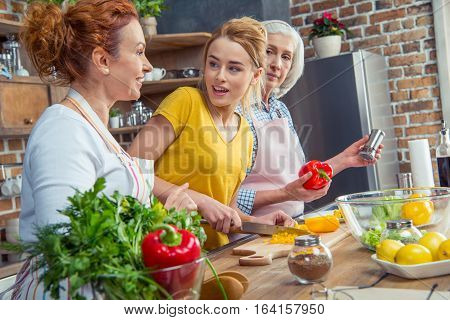 Happy three-generation family cooking together vegetable salad in kitchen