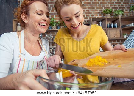 Happy mother and teenage daughter cooking vegetable salad together