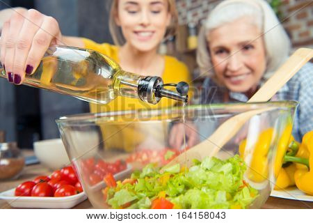 Granddaughter and grandmother cooking together and pouring oil into vegetable salad