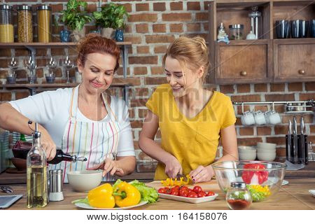 Mother and daughter cooking vegetable salad together