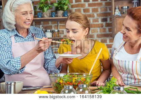 Young woman tasting fresh vegetable salad while standing with mother and grandmother in kitchen