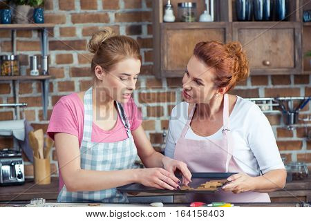 Mother and her teenage daughter making Christmas cookies in kitchen