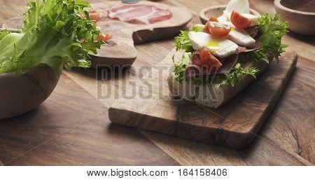 man hands preparing italian sandwich with prosciutto and mozzarella, 4k photo