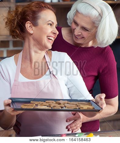 Mother and her adult daughter holding oven tray with Christmas cookies