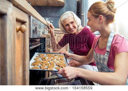 Happy grandmother and her teenage granddaughter removing Christmas cookies from the oven