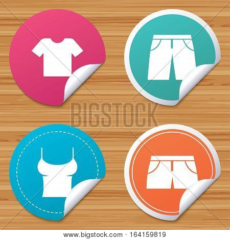 Round stickers or website banners. Clothes icons. T-shirt and pants with shorts signs. Swimming trunks symbol. Circle badges with bended corner. Vector