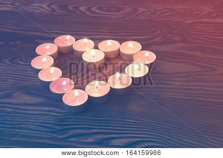 Valentine's day. Heart of candles on brown wooden background