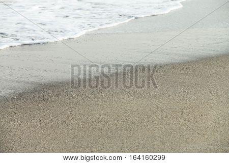Oncoming wave foam on the beach. Black Sea.