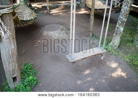 Empty wooden swing in the garden stock photo