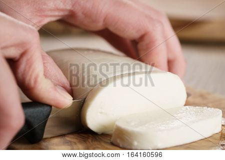 cutting mozzarella cheese on wooden board, shallow focus