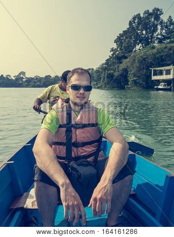 Happy tourist enjoying boat ride. Relaxing on Lake Phewa in Pokhara, Nepal.