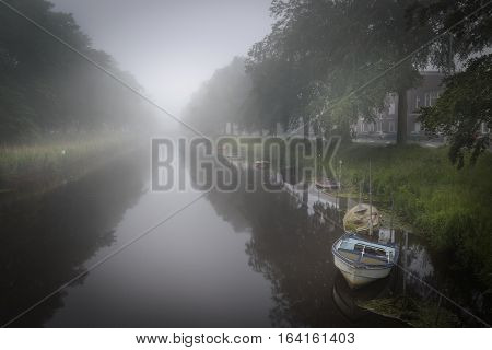 Misty weather in Breda city channel with boats lying calm in the water