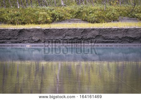 Painting like reflection in blue river water with beautiful textured river bank