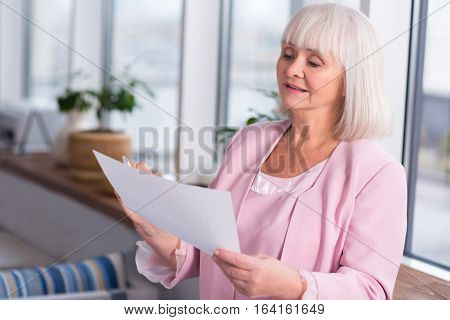 What is that. Mature gorgeous grey haired businesswoman in pink jacket thoroughly reading a report while standing in front of the window for better light