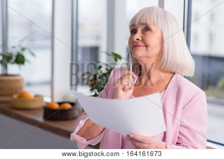 This seems promising. Emotional dreamy senior lady figuring out something after reading a report while thoughtfully holding up a sheet of paper and a pen