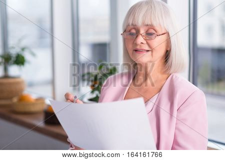A few blunders. Professional mature good looking lady thoughtfully reading a report while holding a pen and making corrections