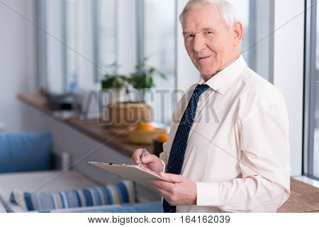 Let us change this part. Experienced enthusiastic elderly executive discussing some points of the report while holding a pen and standing in front of the window