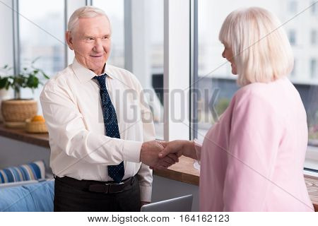 Nice to meet you. Handsome senior executive and a nice grey haired business woman meeting each other for the first time in a restaurant for a business lunch