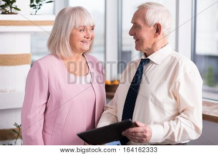 This might be useful. Handsome elderly businessman and enthusiastic mature lady carrying out negotiations on their new project while using a tablet