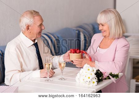 Anything for you. Courteous generous senior man giving his gorgeous lady a little gift while they spending time together in a cafe