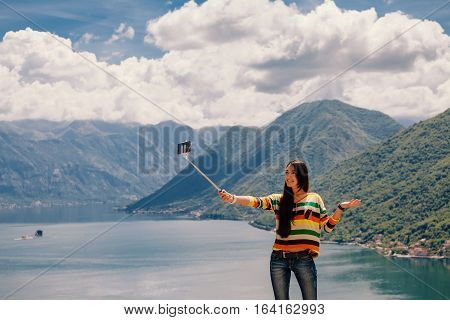joyful woman travel and photo selfie in mountains. Picturesque location in Montenegro Europe.