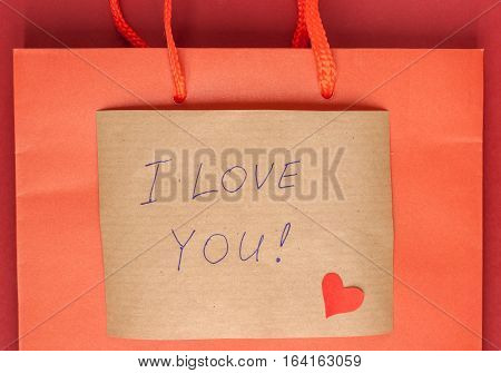 red heart and confession letter attached to paper bag