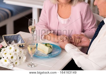 Like love birds. Gallant charming senior man gently holding his ladys hand while they both sitting at the table with a cake and flowers on it