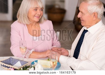 Love in your eyes. Precious elderly woman looking at her companion with tenderness while they both sitting at the table in a restaurant