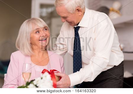 You should not have bothered. Gentle elegant senior man presenting his charming lady a surprise gift for their anniversary