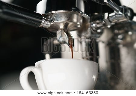 coffee extraction process from professional espresso machine, shallow focus