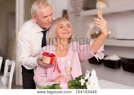 Let us take another one. Charming funny senior lady trying capturing the happy moment at the restaurant with her smartphone