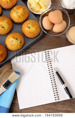 Blank cookbook or writing book on a dark wood table with freshly baked muffins and ingredients.