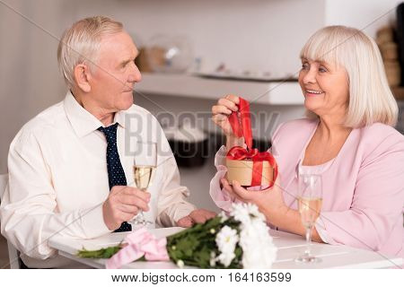 Anything for you, my love. Excited gallant elderly man waiting for his stunning surprise lady opening her present while holding a glass of champagne