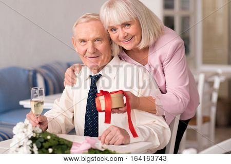 What could be better. Precious happy elderly couple posing for a picture capturing one of the best moment of their lives during their anniversary celebration in a restaurant