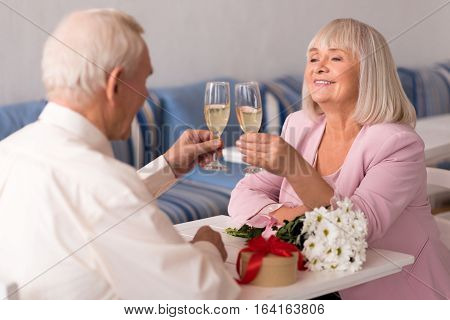 Cheers to our love. Enthusiastic happy senior people sharing champagne at the table in a restaurant while celebrating an important date of their relationship